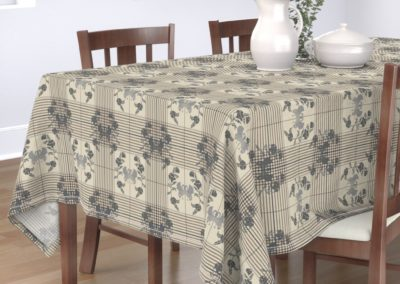 "Tablecloth with art nouveau swans bordered by flowers in half drop on a checked pattern. Main color is ""silver Cloud"" (sand)"