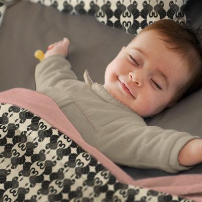 Baby sleeping in Swan Dance duvet cover.
